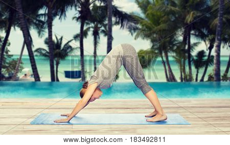 fitness, sport, people and healthy lifestyle concept - woman making yoga in downward facing dog pose on mat over hotel resort pool on tropical beach background
