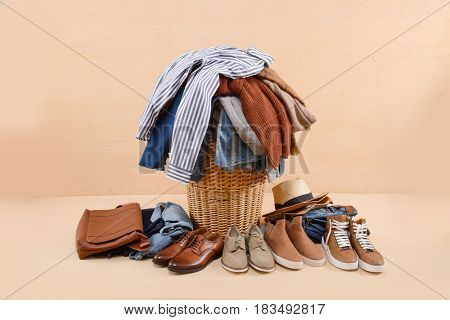 full of jeans, clothes in Basket with bag, shoes, hat -wooden background