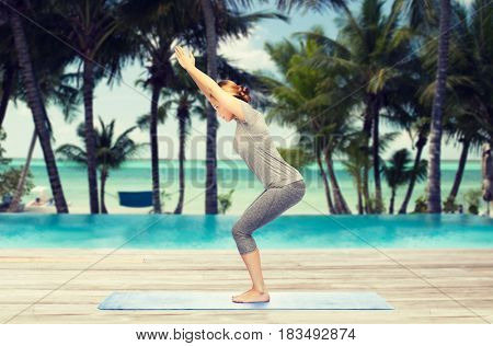 fitness, sport, people and healthy lifestyle concept - woman making yoga in chair pose on mat over hotel resort pool on tropical beach background