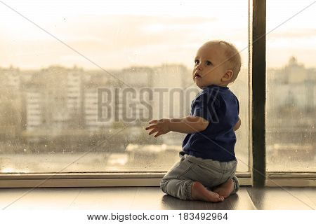 Cute Baby Boy Looking Through The Window To The Rainy Big City. Infant Boy Waiting For The Parents.