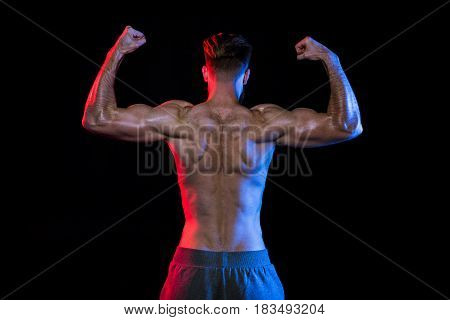 Back View Of Shirtless Bodybuilder Gesturing Isolated On Black With Dramatic Lighting