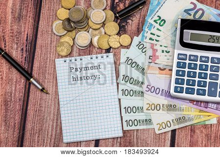Payment history word In notepad with euros calculator coin and pen.