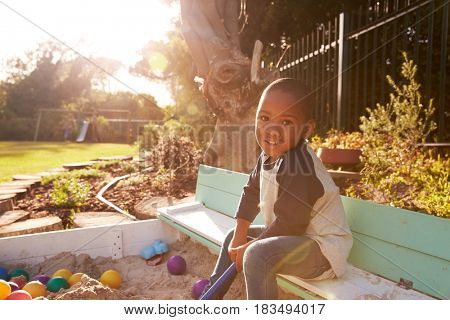 Portrait Of Boy Playing In Sand Box Outdoors In Garden