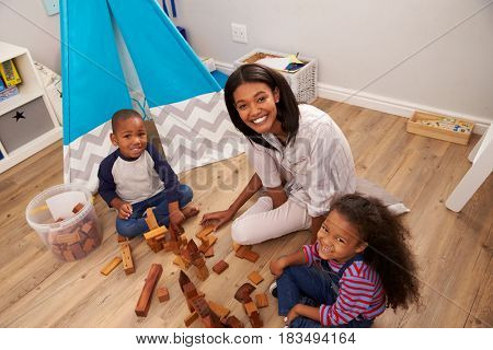 Mother And Children Playing With Building Blocks In Bedroom