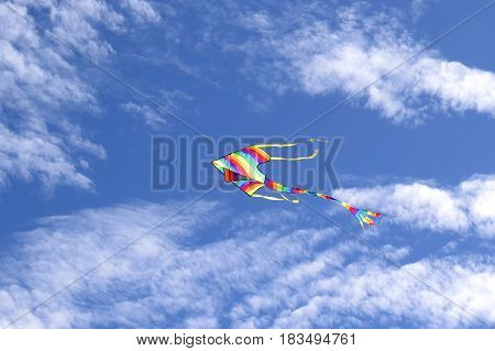 Rainbow kite flying flies fly above Australian beach against a blue cloud sky Summer days