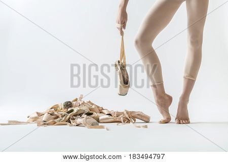 Ballerina stands on the toes and holds a pointe shoe on the ribbon on the light background in the studio. On the left side there is a pile of beige ballet shoes. Closeup. Horizontal.