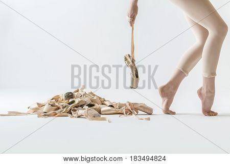 Elegance ballerina stands sideways on the toes and holds a pointe shoe on the ribbon on the light background in the studio. On the left side there is a pile of beige ballet shoes. Closeup. Horizontal.