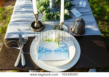 Romantic wedding table setting with candles flowers and invitat