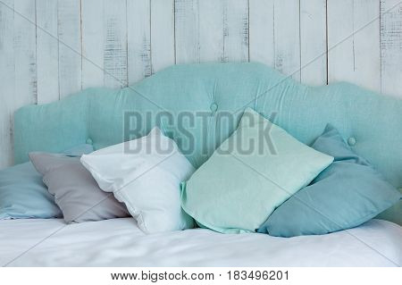 Lots of pillows in blue tones laid out on a bed on a wooden ba