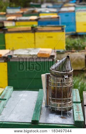 vertical view of metallic bee smoker equipment on top of beehives boxes