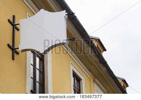 vertical front view of empty coat of arms shaped signage with metallic frame on a building with classical architecture