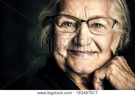 Portrait of a beautiful senior woman in elegant glasses smiling at camera.