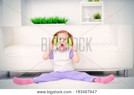 Excited little girl listens to a loud music in headphones at home. Leisure.