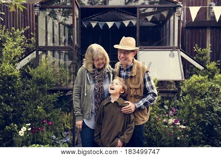 Senior Couple with Little Boy at Home Backyard