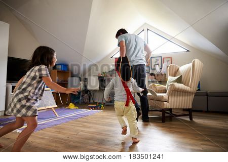 Father Having Game Of Tag With Children In Playroom