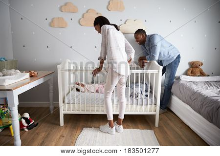 Mother And Father Looking At Baby Daughter In Nursery Cot