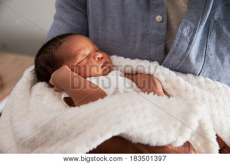 Close Up Of Father Holding Newborn Baby Son In Nursery