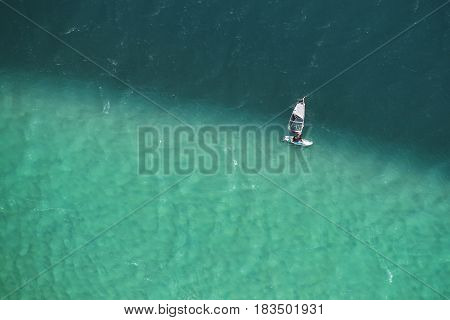 Man windsurfing in two colored sea aerial photo.