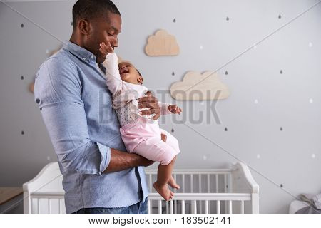 Father Holding Baby Daughter In Nursery