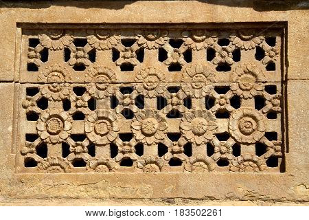 Artistically carved flower petals on stone window at Ladakhan Temple in Aihole Bagalkot District Karnataka India Asia