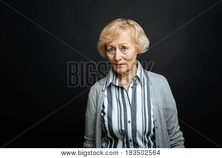 What a pity. Depressed frustrated elderly woman expressing disappointment while standing isolated in black colored studio