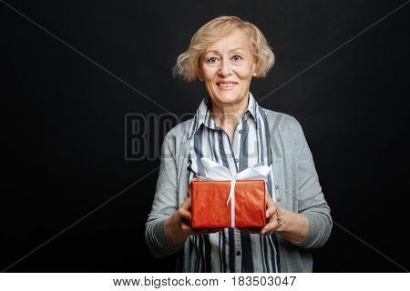 This is for you. Delighted smiling old woman expressing happiness and holding gift box while standing against black background