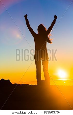 Winner woman winning with open arms in success of reaching mountain top in sunset flare, goal challenge achievement. Sport and active healthy living concept.