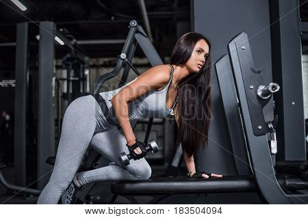 Training in the gym. Fitness girl to build up muscles with dumbbells. Fitness trainer to warm up. Workout on the triceps tone muscles