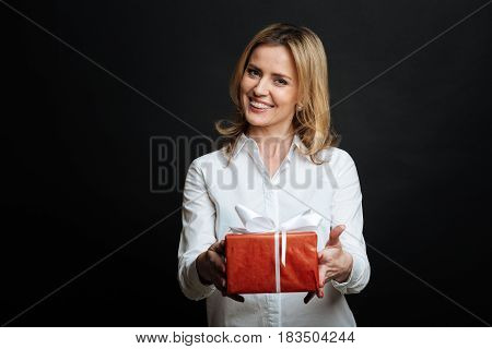 With all my love to you. Loving kind young woman expressing positivity and demonstrating gift box while standing against black background