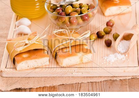 Focaccia bread with olives on cutting board.