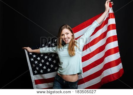 Proud to represent the USA citizenship . Amused young cheerful woman smiling and expressing joy while holding USA flag and standing isolated in black background