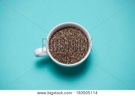 Nutritious chia seeds in cup on light blue background.