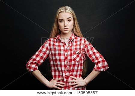 Sure in my choice. Attractive concentrated confident teenager expressing self reliance while demonstrating readiness for action and standing against black background