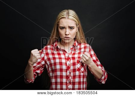 Defending myself. Aggressive emotional confident teenager expressing anger and demonstrating readiness for fight while showing fists and standing isolated in black background