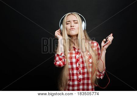 Music in my life. Delighted positive young girl expressing joy and using headphones and phone while listening to the music and standing isolated in black background