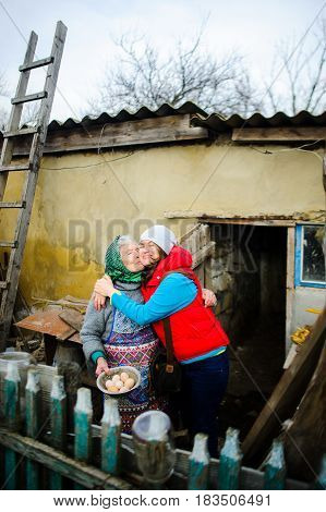 The young woman embraces the old woman. Love and tenderness of the granddaughter and grandmother. Rural farmstead.