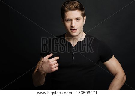 Enjoying provocation . Joyful resolute athletic man expressing positivity while gesticulating and standing against black background