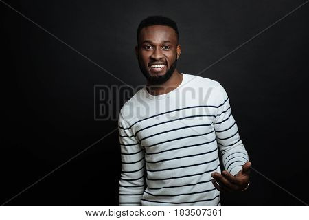 Full of joyful emotions. Optimistic friendly African American man expressing joy and smiling while standing against black background