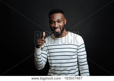 Nice to meet you. Charming delighted African American man expressing delight and smiling while standing isolated in black background