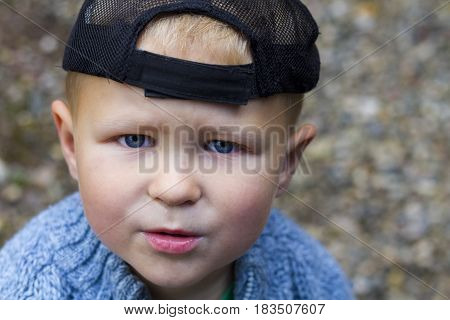 Portrait of cute boy in a cap little bit worried