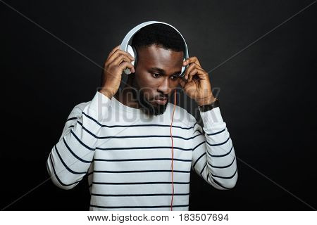 Meditating on my destiny. Young peaceful African American man using headphones and listening to the music while standing isolated against black background