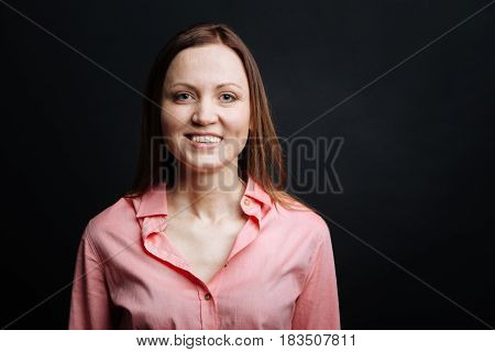 Sharing optimism. Young beautiful optimistic woman expressing positive emotions and smiling while standing isolated in black background