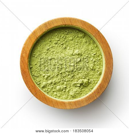 Green matcha tea powder in bowl isolated on white background. Top view.