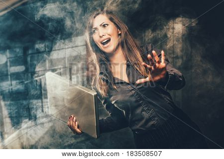 Worried business woman with laptop. Dark background.