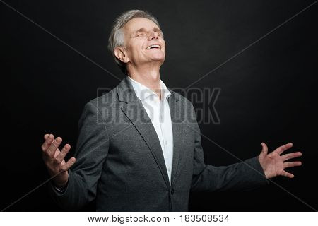 In harmony with world. Relaxed aged delightful pensioner expressing positivity and raising hands above while standing against black background
