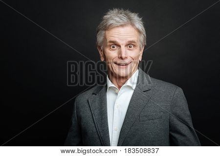 Joyful surprise for me. Pleasant surprised old man smiling while expressing puzzlement and standing against black background