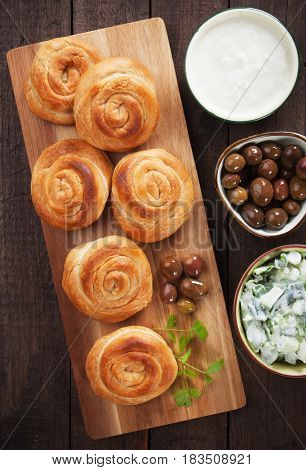 Phyllo pastry cheese pies served with yogurt, olives and salad