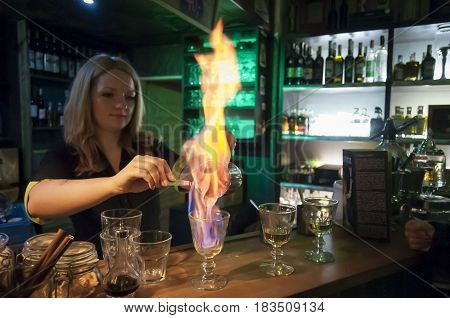 PRAGUE, CZECH REPUBLIC. January 24, 2016. Unknown  bartender girl in a Czech bar Absintherie (Absinthe Museum) in central Prague showing proper absinthe drink preparation.