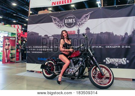 St. Petersburg Russia - 15 April, A fashion model on a motorcycle at the banner,15 April, 2017. International Motor Show IMIS-2017 in Expoforurum. Models on motorcycles presented at the motor show.