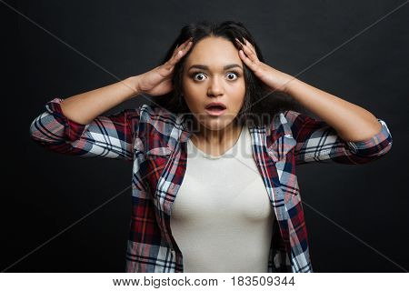Difficult to believe. Young astonished Hispanic American woman feeling frustrated and touching her head while standing isolated in black background
